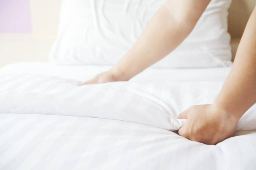 A woman hand setting up the comforter on a bed