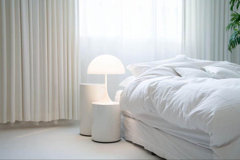 A white comforter on a bed with pillows