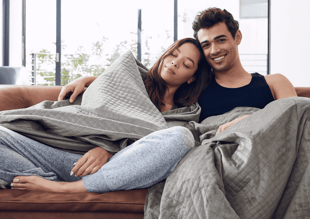A Happy young couple cuddling weighted blanket