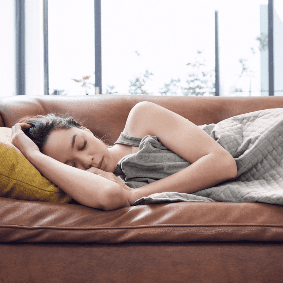 Young girl sleeping on couch with weighted blanket cuddled