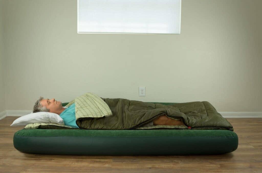 A Man Sleeping on the Floor With Mattress