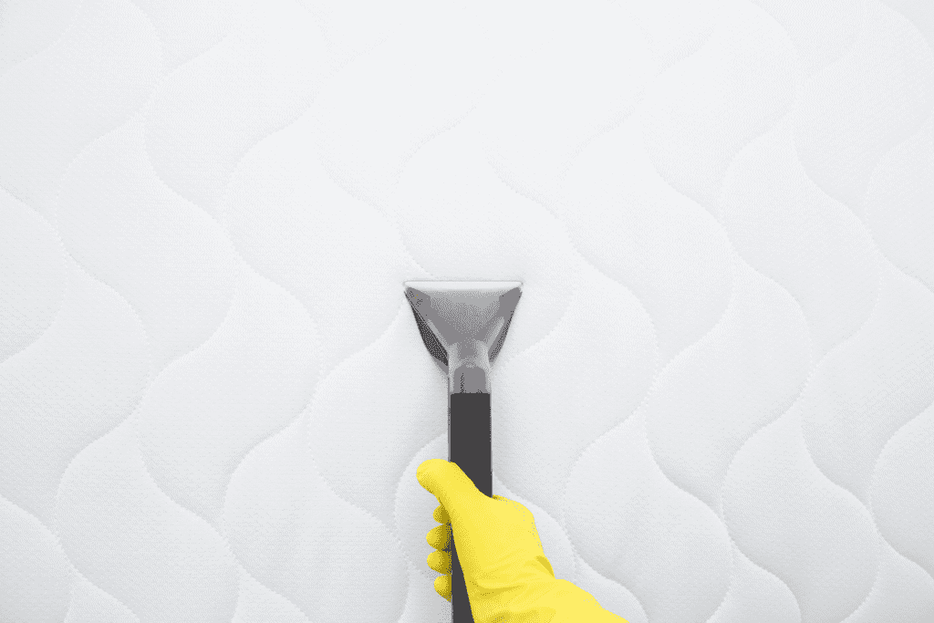 Man cleaning a mattress from dust and bacteria with a vacuum before storing it