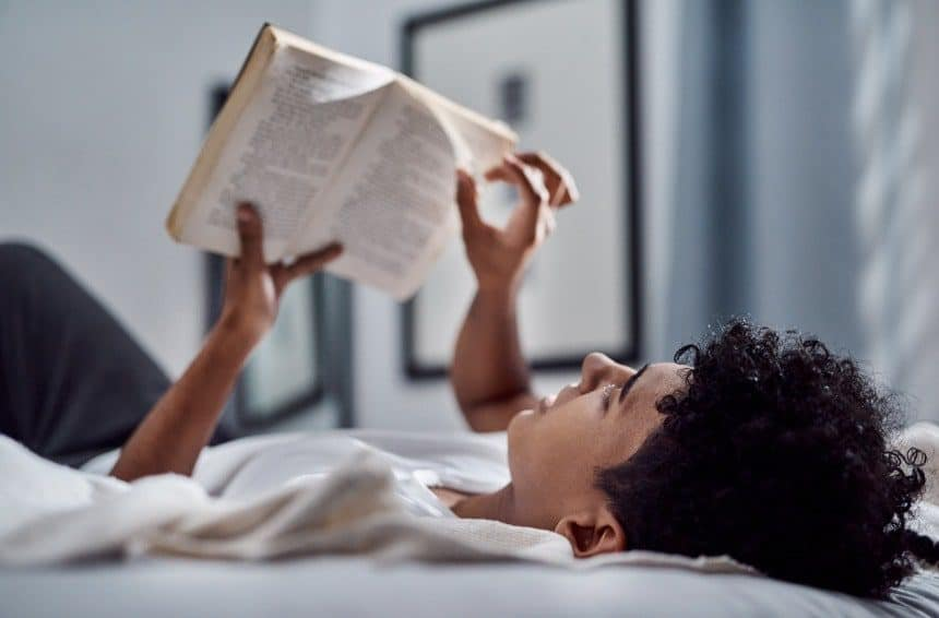 A Young Man Reading a Book on His Bed
