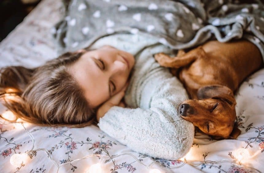A young woman sleeping with her puppy in bed