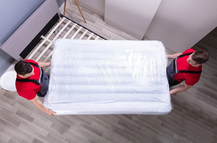 Two young professional movers moving a mattress