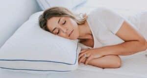A woman sleeping with a pillow on mattress