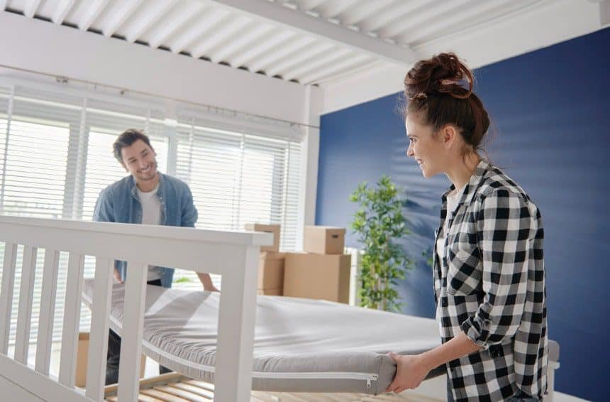 A couple putting a mattress on a bed after moving it from other place