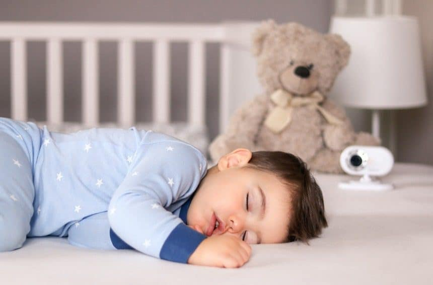 A cute little baby boy in light blue pajamas napping peacefully on bed