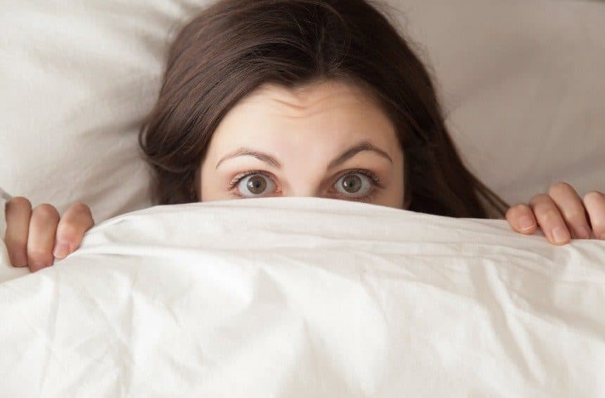 Girl covering half of face with white blanket due to nightmare or fear in sleep