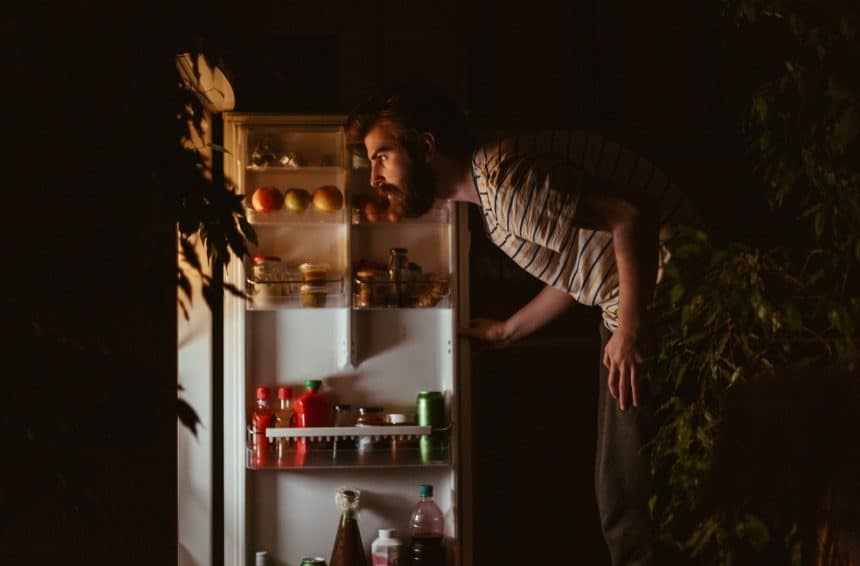 Man looking for snacks in the refrigerator in late night