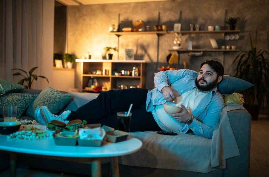 Lazy man lying on side on sofa and watching TV while eating popcorn late night