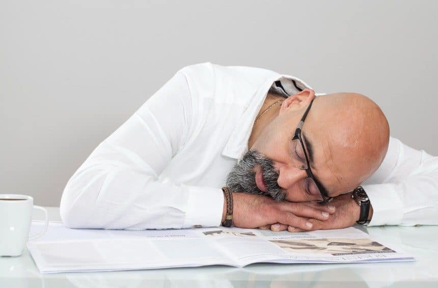 Middle aged man goes into nap on table while reading newspaper