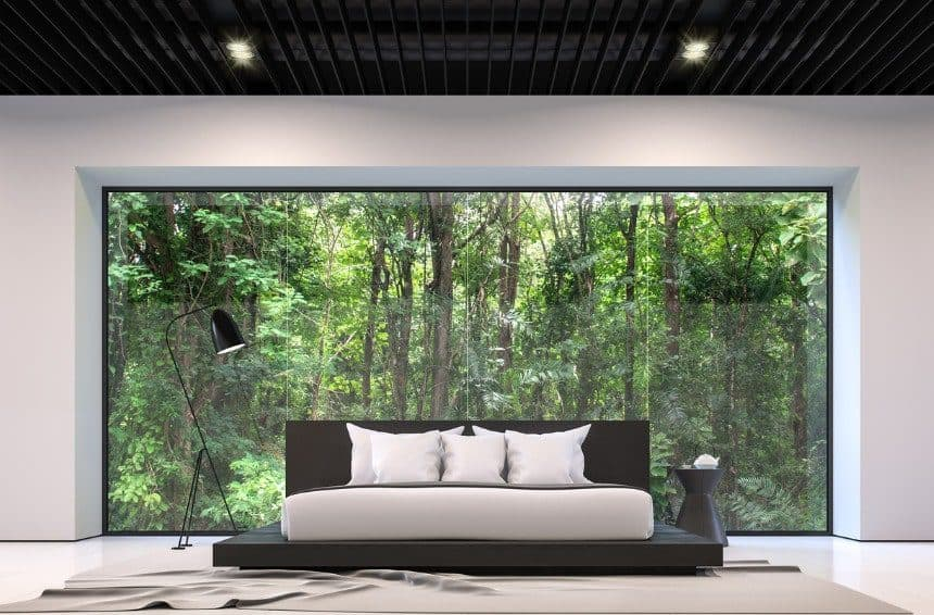 Oversized bed in beautiful bedroom with forest view