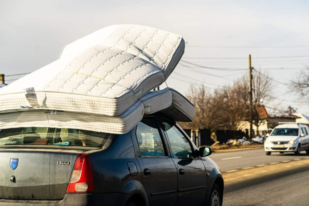 A Car carrying mattresses on its roof
