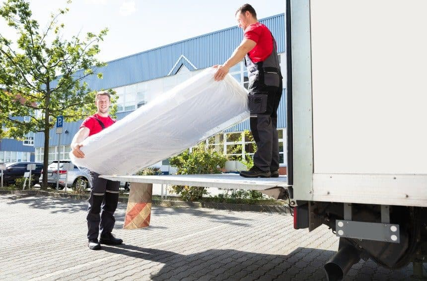 Two professional men moving a mattress in a covered truck for transporting it to mattress storage unit