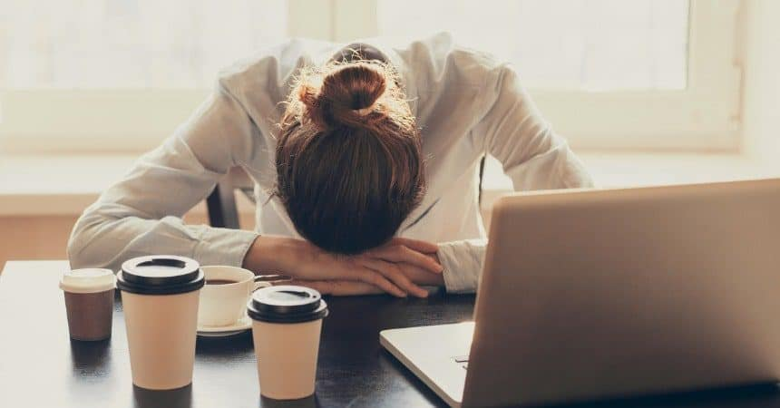 Tired Woman in the Office With Cup of Tea and Coffee in Front of Her