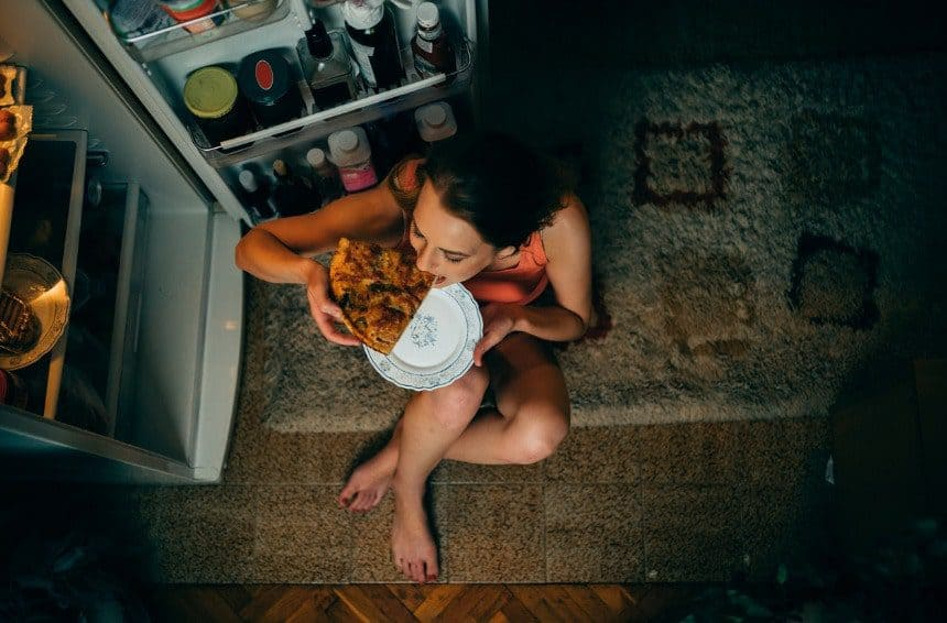 Woman eating in front of the refrigerator in the kitchen at late night